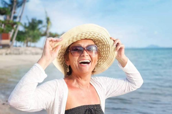 Happy woman in a hat at the beach