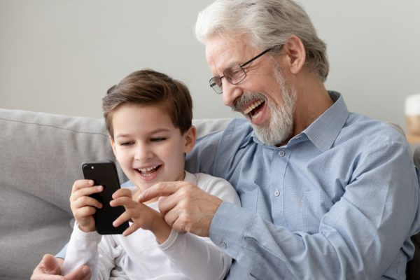 man sitting on a couch with his grandson as they both laugh while looking at a smartphone