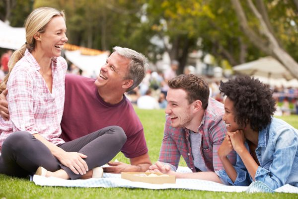 parents with their adult son and his girlfriend sitting in a park and laughing